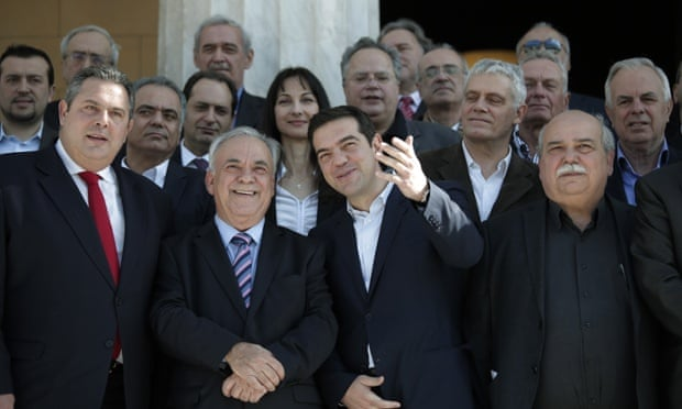 Alexis Tsipras, accompanied by members of his government, poses for a group picture outside the parliament in central Athens.