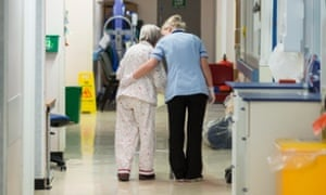 A health worker and patient on a ward in Addenbrooke, one of the hospitals which refused to sign off the NHS budget deal.
