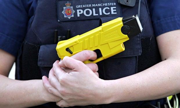 A Greater Manchester police officer holds a Taser stun gun