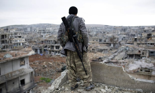 A Syrian Kurdish sniper looks at the rubble of Kobani, which Islamic State controlled half of before being driven from the town.