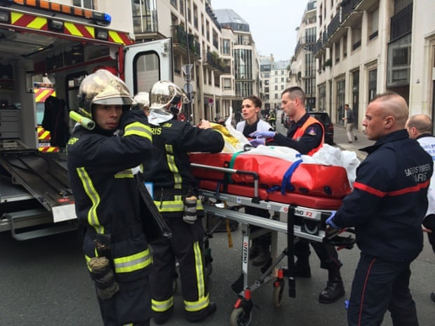 Firefighters carry an injured man out of the Charlie Hebdo offices