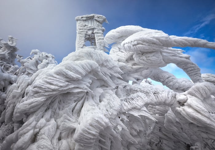 Heavy frost and large ice spike formations envelop a watchtower and trees at Mount Javornik on December 9, 2014 in Javornik, Slovenia.  THESE incredible ice formations were created when freezing fog descended on a mountain range. The images were captured by photographer Marko Korosec who travelled to the top of Mount Javornik in Eastern Slovenia and noticed that hard rime had been accumulating in the mountains. Hard rime is a white ice that forms when the water droplets in fog freeze onto a surface.