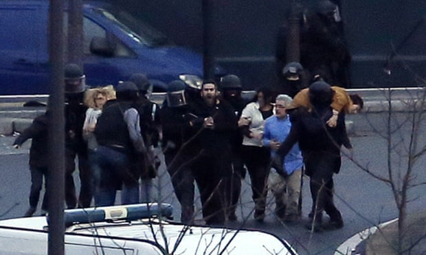 Members of the French police special forces evacuate the hostages after launching the assault at a kosher grocery store in Porte de Vincennes, eastern Paris.