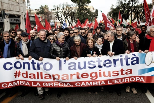 People hold a banner reading 'against austerity, Greece change, Europe change' at a rally in Rome