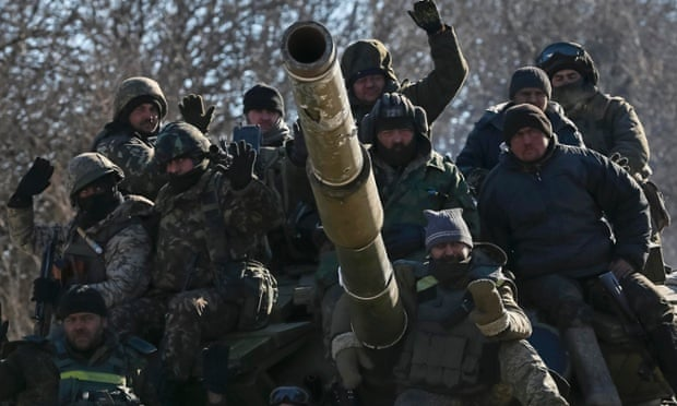 Servicemen ride on a tank as they leave Debaltseve.