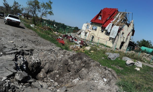 The crater of a shell strike gapes near a wrecked building in Simonovka district.