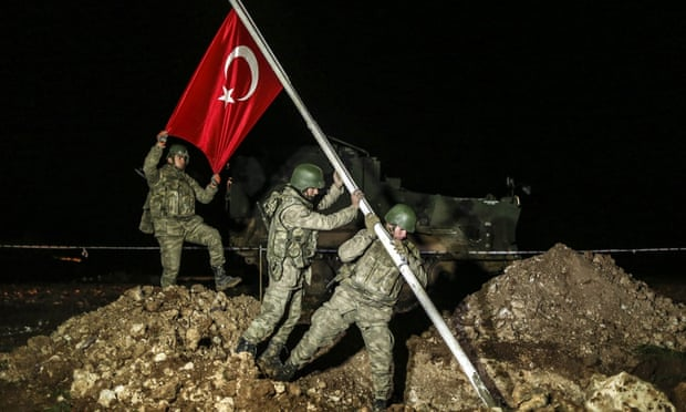 Soldiers raise a Turkish flag in the Esme region of Syria where the remains of Suleyman Shah have been relocated.