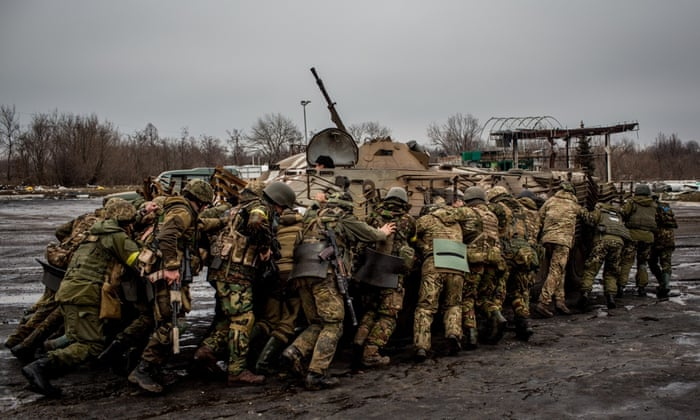 Ukrainian soldiers try to push-start an armoured personnel carrier at a military checkpoint in Debaltseve