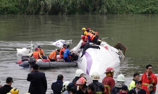 Rescuers pull a passenger out of the TransAsia Airways plane which crash landed in a river, in New Taipei City, February 4, 2015. At least two people killed after a TransAsia Airways plane carrying 58 people crash landed in Taipei River, government said. REUTERS/Pichi Chuang
