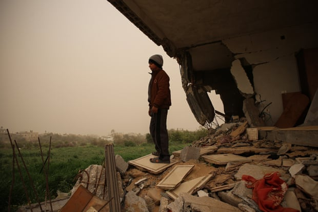 Sabeha's grandson, Hareth stands on the hill of a rubble where his room once was
