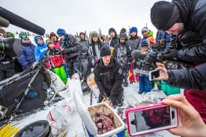 2014 Iditarod winner Dallas Seavey gives an interview to members of the media as he makes food for his dogs shortly after arriving at the Koyuk checkpoint