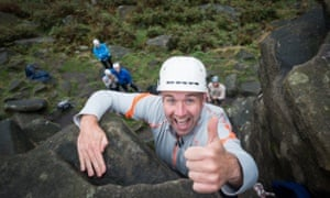A happy man rock climbing, holding his thumb up in approval