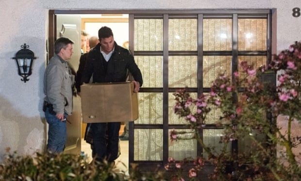 Police carry computer, a box and bags out of the residence of the parents of Andreas Lubitz.