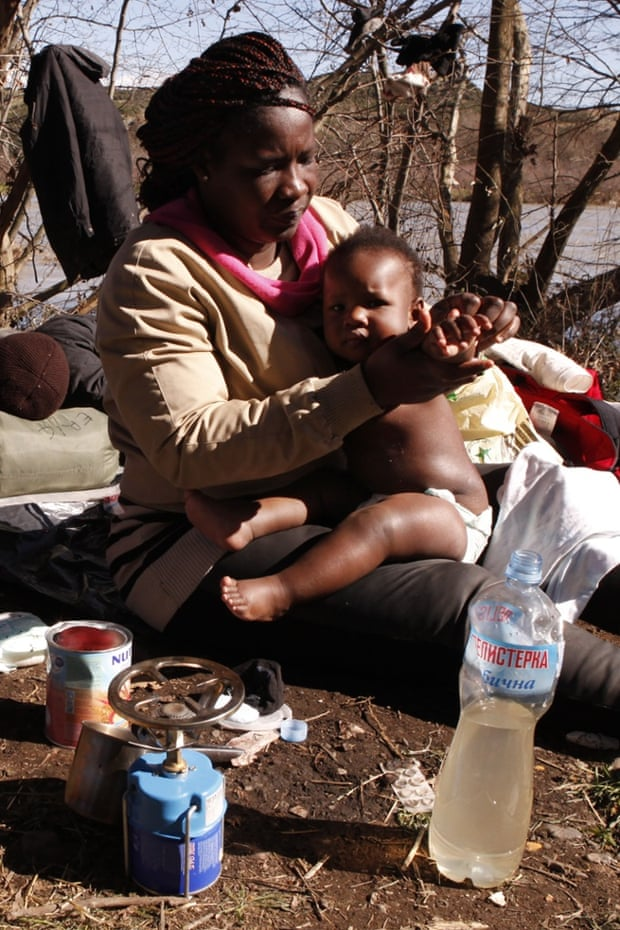 Sandrine Koffi washes her daughter Kendra with river water during a rest near the village of Marvintsi, Macedonia, in early March.