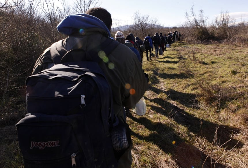 West African migrants walk near the village of Udovo, Macedonia.