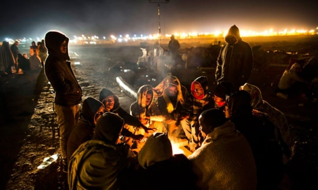 African asylum seekers gather around a fire during protests outside the Holot detention centre in the Negev