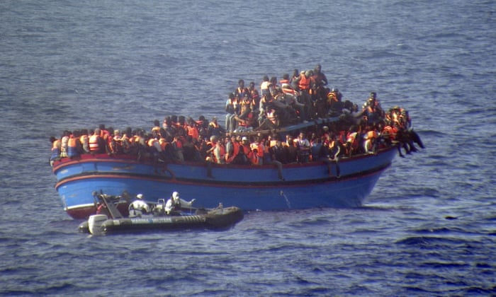 A motor boat from the Italian frigate Grecale approaches a boat overcrowded with migrants in the Mediterranean
