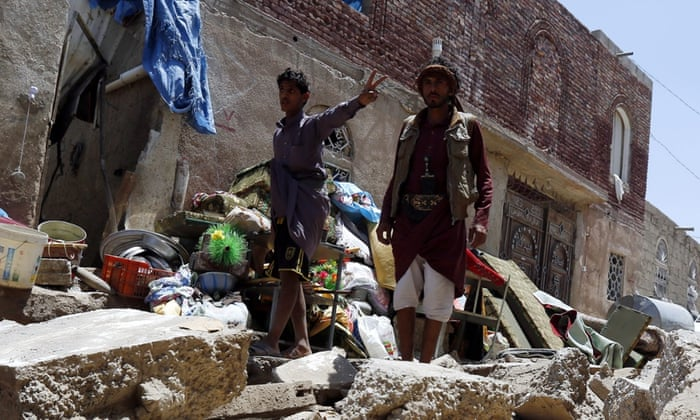 Yemenis collect their belongings after their houses were hit by an airstrike in Sana'a. Many are fleeing to neighbouring countries, threatening to overload refugee camps.