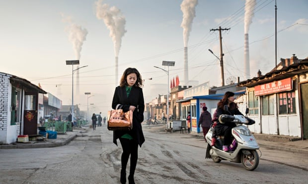 Woman walks through smoke stacks in Shanxi Province, China