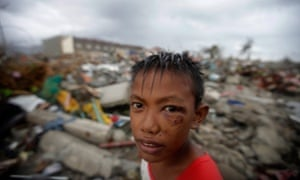 Typhoon Haiyan survivor Joshua Cator, 11, scavenging for food and reusable material in destroyed houses.