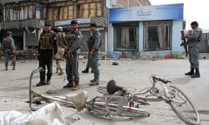 Afghan policemen inspect the site of the suicide bombing in Jalalabad on Saturday morning.