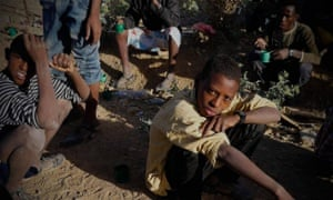 Teenage Eritrean migrants fleeing their country's harsh  compulsory recruitment policy rest in Ethiopia after crossing the border.