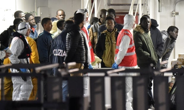 Libyan migrants stand on the deck of an Italian coastguard ship