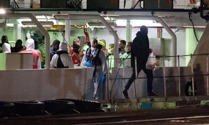Migrants who survived the Mediterranean shipwreck arrive in Catania, Sicily, aboard an Italian coastguard vessel.