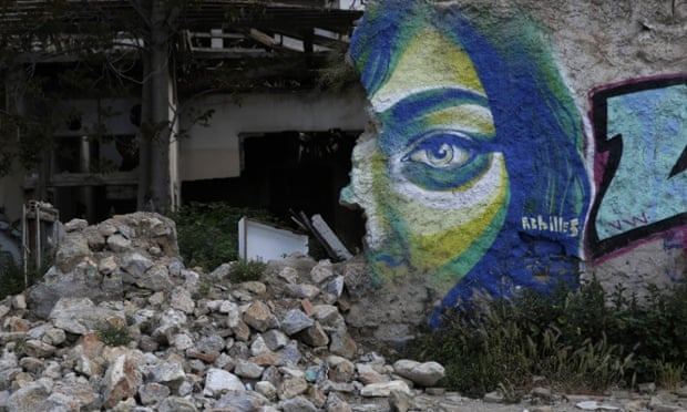 Graffiti by Greek street artist Achilles is seen on a wall of an abandoned house in central Athens, on Wednesday, April 22, 2015.