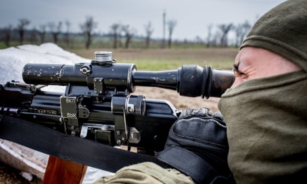 A fighter of the Ukrainian volunteer Azov Battalion aims through the scope of his weapon at rebel-controlled territory in Shyrokine, Ukraine.