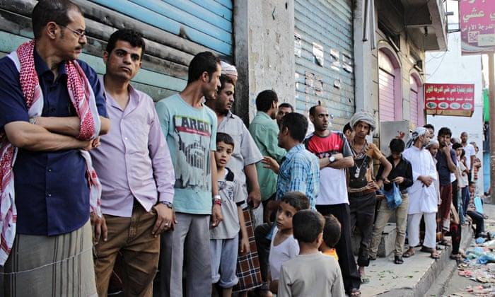 Yemenis wait in line to buy bread