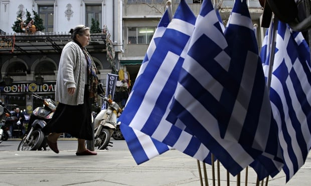 A woman walks past Greek flags for sale in central Athen. Greece is running perilously short of cash
