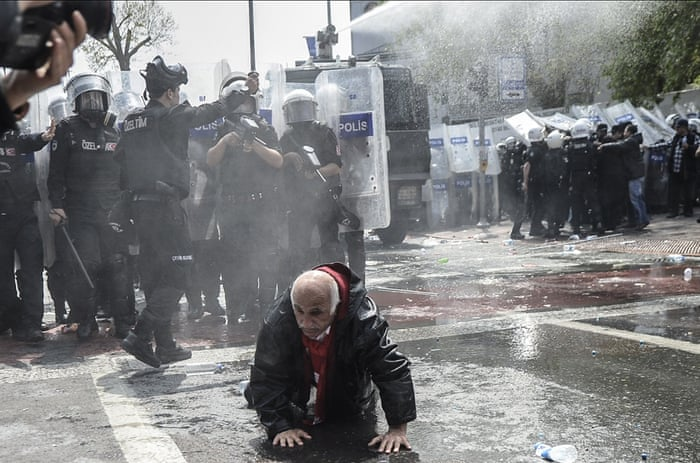 <strong>Istanbul, Turkey </strong>An elderly man attempts to get up off the ground near a row of riot police after Turkish police use a water cannon to disperse protestors during a May Day rally near Taksim Square