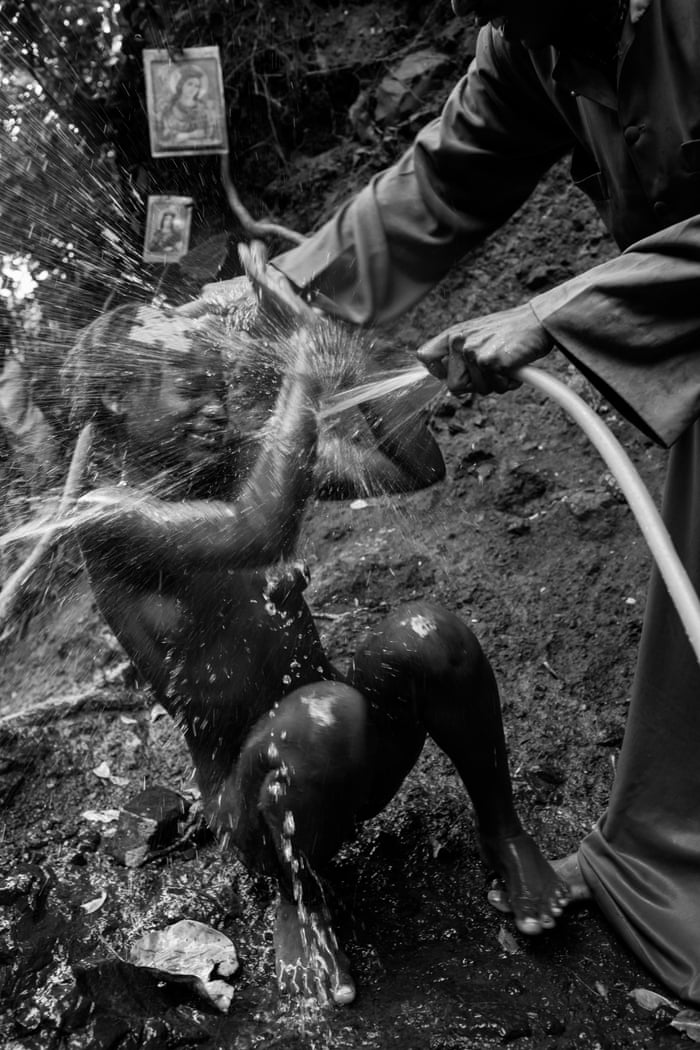 A  girl is sprayed and struck with a cross by the priest. Exorcism rituals may be linked to tribal religions that pre-date the arrival of Christianity in Ethiopia