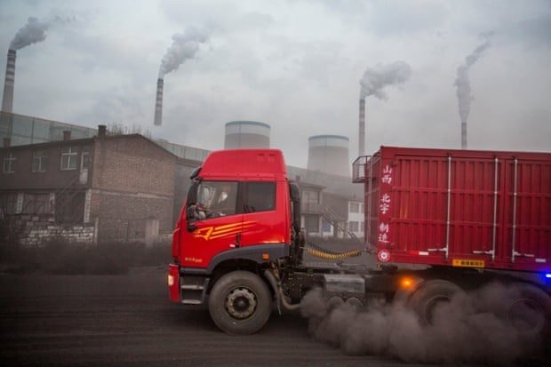 07 Nov 2013, Datong, Shanxi Province, China --- China, Shanxi Province, Datong, Trucks driving along dust-covered access road to deliver coal to Datong No. 2 Power Station