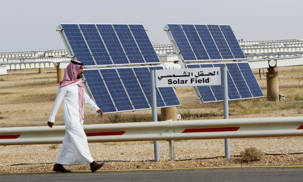 A Saudi man walks on a street past a field of solar panels at the King Abdulaziz city of Sciences and Technology in May 2012.