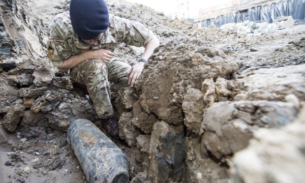 An army bomb disposal expert inspects an unexploded second world war bomb found in Wembley, north London. Photograph: Sergeant Rupert Frere/AP
