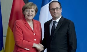 Angela Merkel and François Hollande shake hands in Berlin.