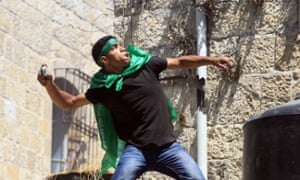 A Palestinian protester, wearing a headband and scarf in support of Hamas, throws stones during clashes with Israeli security in the West Bank town of Hebron in August 2014.