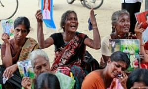 Sri Lankan ethnic Tamil women hold portraits of missing relatives during a protest in Jaffna, Sri Lanka, in 2013.