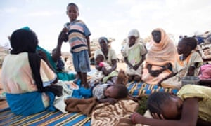 A group of women and children shelter at the Kalma camp for internally displaced people in South Darfur.