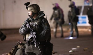 A police officer patrols in Ferguson, Missouri, during protests over the shooting death of Michael Brown.
