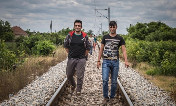 A group of Afghan migrants walk along the train tracks.