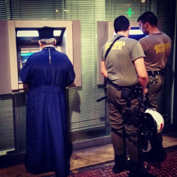 A Greek priest uses a cash machine in Athens tonight, alongside two riot police officers.