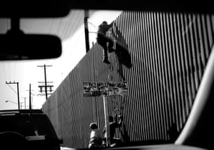 An unidentified man is seen climbing over the international border dividing Mexicali, Mexico, from Calexico, California
