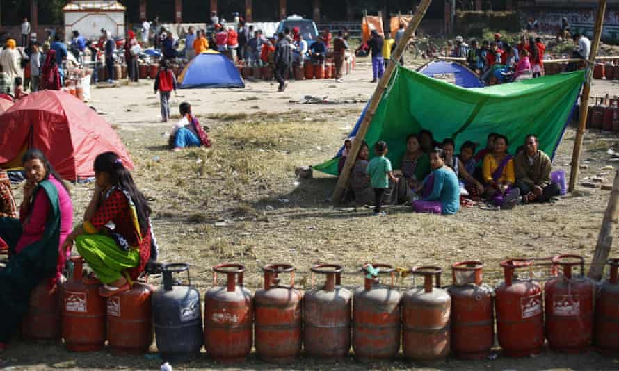 Nepalese citizens sit in temporary shelters as they queue for cooking gas cylinders in Kathmandu