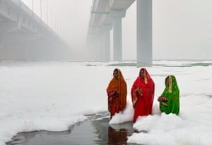 Women worship in the polluted Yamuna River, India