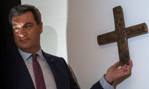 Markus Söder hangs a cross in the entrance area of the Bavarian state chancellery