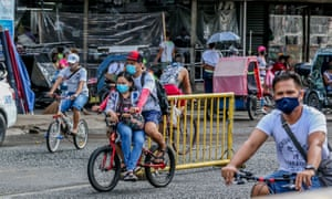 People wearing face masks ride along a street in Manila, the Philippines on 10 July 2020.