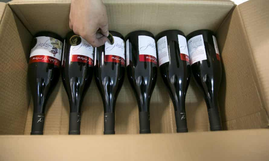 A worker places stickers on wine bottle